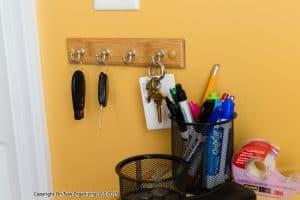 A key hook, pen cup & change jar in a drop zone