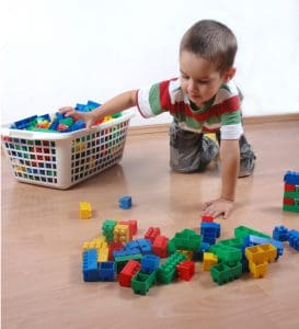 A boy putting blocks in a laundry basket